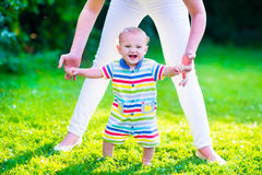 Little baby boy making first steps. Baby boy making his first steps. Mother holding her child. Kid walking on a lawn in a sunny summer garden. Kids learning to Stock Image