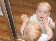 Little baby boy in mirror reflection. Little baby boy with blue eyes in mirror reflection Stock Photo
