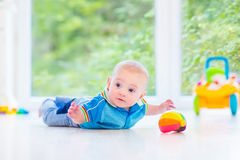 Little baby boy playing with colorful ball and toy car. Adorable baby boy playing with a colorful ball and toy car in a white room Stock Images