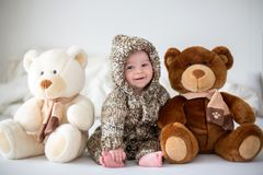 Little baby boy playing at home with soft teddy bear toys, lying. Little baby boy playing at home with soft teddy bear toys, sitting in bed stock photos