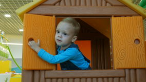 A little baby boy playing in a little house and opening the windows