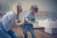Little baby boy playing with Mom in living room. Childhood stock images
