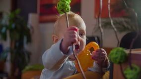 Little baby boy playing with plant. Slow motion close up footage of a little happy baby boy playing with plant in the middle of the living-room with plastic toy stock video footage