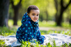 Little baby boy playing on the playground in the spring park. Black boy royalty free stock image