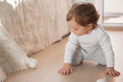 Little baby boy playing with silver Christmas balls Royalty Free Stock Image