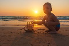 Little baby boy is playing with toy ship on the sand of amazing tropical beach of Andaman sea in Thailand at sunset. royalty free stock images