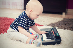 Little baby boy plays on keyboard toy. Baby piano music playing child white cute little concept Stock Photo