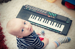 Little baby boy plays on keyboard toy. Baby piano music playing child white cute little concept Royalty Free Stock Images