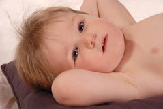 Little baby boy poses for camera laying on pillow. Little baby boy poses for camera on white crinkled background. laying on pillow arms behind head Royalty Free Stock Images
