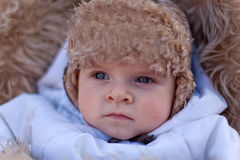 Little baby boy in pram in winter clothes. With snowfall Royalty Free Stock Image