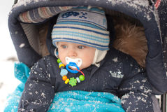 Little baby boy in pram in winter clothes. With snowfall Stock Image