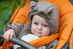 Little baby boy in pram in winter clothes. Little adorable baby in orange pram Royalty Free Stock Photo