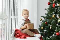 Little baby boy with present in his hands sitting near Christmas tree and looking at camera. Royalty Free Stock Images