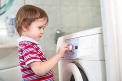 Little baby boy programming washing machine in bathroom Stock Photos