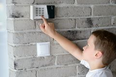 Little baby boy pushes a buttons on the alarm keypad. Home security system mounted on wall Royalty Free Stock Images