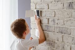 Little baby boy pushes a buttons on the alarm keypad. Home security system mounted on wall stock photos