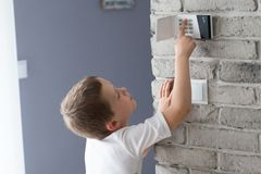 Little baby boy pushes a buttons on the alarm keypad. Home security system mounted on wall stock photography