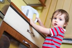 Little baby boy is reaching eletrical kettle with hot water. Danger in kitchen Stock Photos