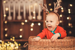 Little baby boy in reindeer antlers sitting in a wicker basket Royalty Free Stock Photography