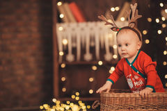 Little baby boy in reindeer antlers sitting in a wicker basket. Royalty Free Stock Photography