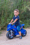 Little baby boy riding  motobike. Little baby boy riding on the blue motobike Royalty Free Stock Photo