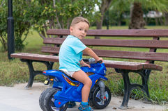 Little baby boy riding  motobike. Little baby boy riding on the blue motobike Royalty Free Stock Photography