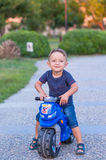 Little baby boy riding  motobike. Little baby boy riding on the blue motobike Royalty Free Stock Photos