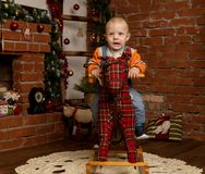 Little baby boy on rocking horse, dressed in sweater and jeans. Christmas or New Year decorations stock image