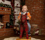 Little baby boy on rocking horse, dressed in sweater and jeans. Christmas or New Year decorations stock photography