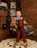Little baby boy on rocking horse, dressed in sweater and jeans. Christmas or New Year decorations royalty free stock photo