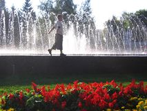 Little baby boy running around near the fountain playing under the streams of water rejoices beautifully stock images