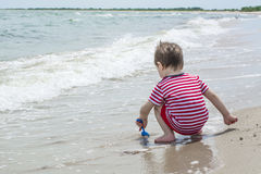 Little baby boy sat down closer to the water and playing with sand shovel on the beach. Royalty Free Stock Image