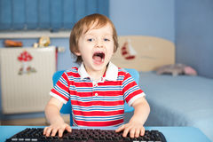 Little baby boy screaming when typing on keyboard. In his room Royalty Free Stock Photography