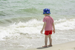 Little baby boy is on the sea wets feet in water. Stock Images