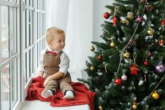Little baby boy sittiing near window and looking on Christmas tree. Holidays, gift, and new year concept Stock Photography