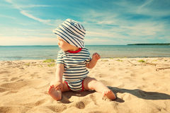 Little baby boy sitting on the beach in summer day stock photos