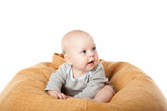 Little baby boy sitting in bean bag. Chair isolated over white royalty free stock images