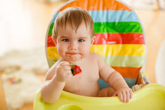 Little baby boy sitting in a bright chair, eating strawberries royalty free stock photography