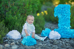 Little baby boy sitting close to number one birthday number blue color.  Royalty Free Stock Photography