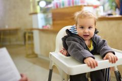Little baby boy sitting in high chair in cafe.  stock images