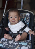 Little baby boy sitting in a stroller, ready for a walk in a pra Royalty Free Stock Photography