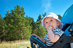 Little baby boy sitting in the stroller on summer day Stock Images