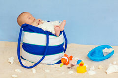 Little baby boy, sleeping in a bag. Little baby boy, sleeping in a blue bag, toys around Royalty Free Stock Images