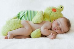 Little baby boy, sleeping with big teddy frog. In bed Stock Photos