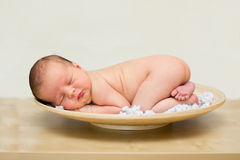 Little baby boy, sleeping in a plate. On the table Royalty Free Stock Image