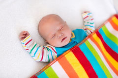 Little baby boy sleeping under colorful blanket. Newborn baby boy in bed. New born child sleeping under a colorful blanket. Children sleep. Bedding for kids Royalty Free Stock Images