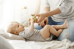 Little baby boy spending happy childhood with young mother. Child trying to take a beautiful toy from tender mom hands. Family concept Royalty Free Stock Photography
