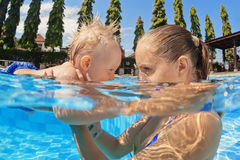 Little baby boy swimming in outdoor pool with mother royalty free stock photo
