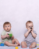 Little baby boy and toddler girl playing with toys. Two cute kids in the grey background playing toys and looking at camera. Vertical shot Stock Images