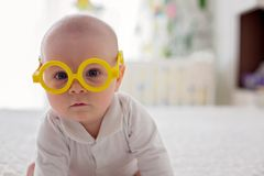Little baby boy, toddler, playing at home with funny eye glasses. In bed in bedroom royalty free stock images